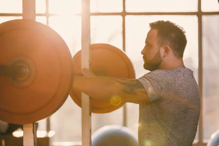 Man ready to squat with barbell in a fitness gym making his muscles more strong