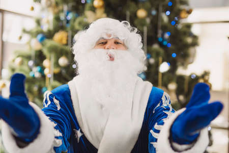 Blue Santa blowing a cold wind breathing from hands