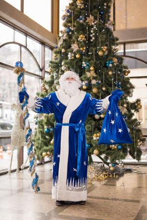 Blue Santa celebrating New Year holiday against Christmas tree, full-length portrait