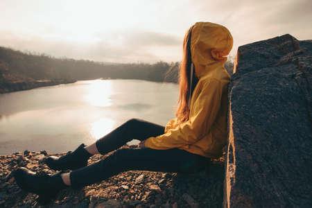 Traveler woman looking at sunset sitting near lake