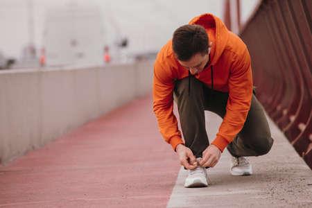 Athlete runner man tie shoelaces on his sneakers on a bridge