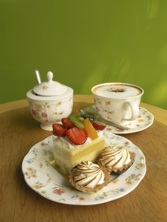 Cup of Coffee, piece of cake on the table and green background    Stock Photo - 14601927