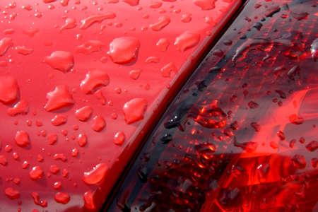 Detalle de gotas en un coche rojo Foto de archivo