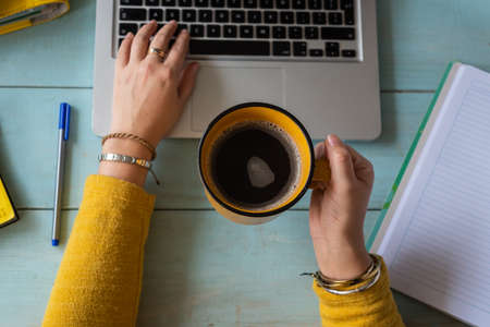 Hands of a woman with a cup of coffee worked on her laptop. Work at home concept.