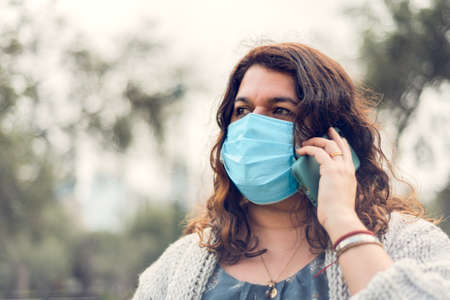 Young woman protecting herself with a medical mask enjoys being in outdoor park sitting on a bench in the new normal. Concept of the new normal. Copy space. Banco de Imagens