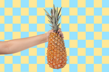 Woman hand holding pineapple colorful background Banco de Imagens