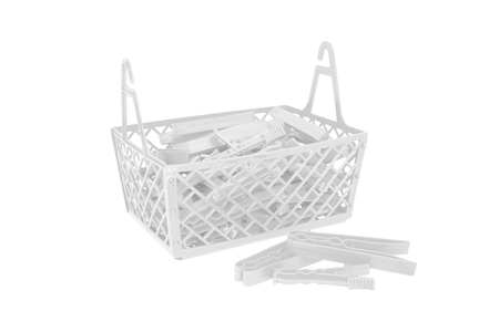 Pile of color plastic cloth clamps inside basket isolated on white