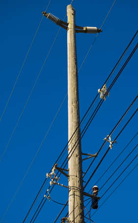 electrical power: Electrical power lines and utility pole with communication lines against a blue sky at dusk.