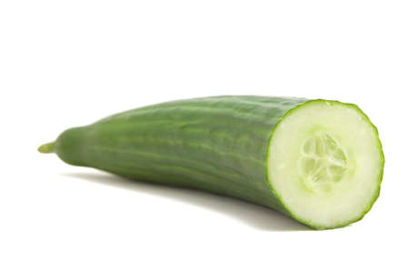 unsliced: A fresh cut cucumber on white background. Focus on cut end of cucumber. Stock Photo
