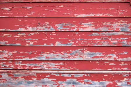 Red peeling paint on an old wooden wall photo