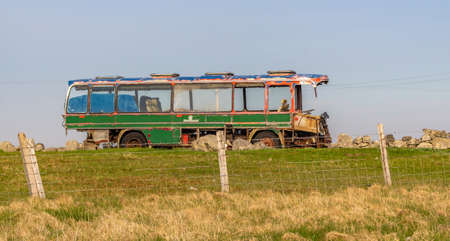 Derelict green bus on a hill Stock Photo