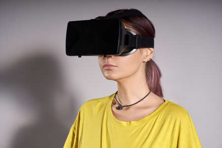 presence: Woman in VR headset looking up and trying to touch objects in virtual reality. VR is a computer technology that simulates a physical presence and allows the user to interact with environment. Stock Photo