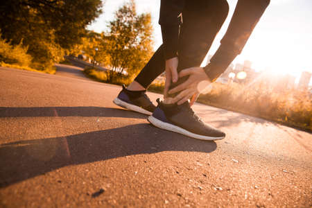sprained joint: Broken twisted ankle - running sport injury. Athletic man runner touching foot