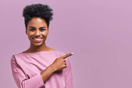 Horizontal portrait of happy dark skinned mixed race female model indicates with fore finger at blank copy space, shows place for your advertisement or promotional text. Lovely African American girl Banco de Imagens