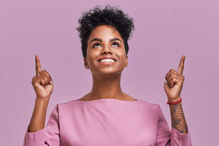 Joyful pretty African American female indicates with both fore fingers up, has friendly smile, dark skin, curly hair, shows blank space against lavender background. People, advertisement concept Фото со стока