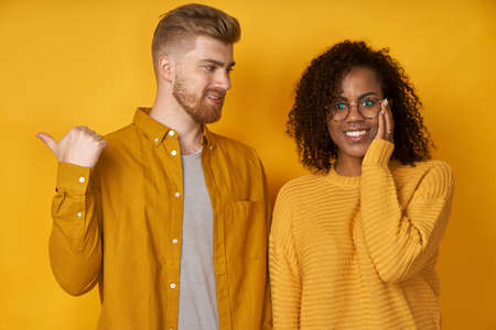 Studio shot of cheerful woman hears advice from boyfriend who tells something and points aside with thumb, dressed in similar yellow t shirts, being friendly team of coworkes. Lets go there Imagens