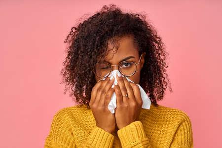 Retrato de una mujer afroamericana enferma que estornuda en un tejido blanco, sufre de rinitis y secreción nasal, tiene alergia a algo, se ve poco saludable, se siente mal. Síntomas de resfriado o alergia. Foto de archivo