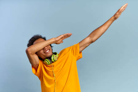 Cheerful African-American young guy joyfully raises hands up covering face as dub dancing sign posing on blue background with headphones in yellow t-shirt. ?oncept of music subscription, online radio