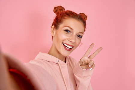 Emotional pretty caucasian red-haired woman with toothy smile in pink hoodie makes peace sign, takes selfie via modern smartphone on pink background. Concept photos for social networks and gadgets