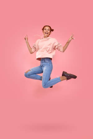 Full length shot of happy cheerful red-haired beautiful young girl in casual clothes jump in air on a pink background. Concept of happy news and promotions for youth. Advertising space
