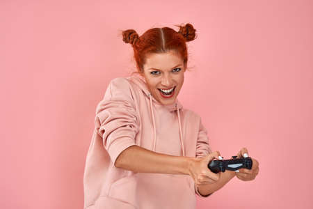 Smiling red-haired girl teenager playing with the joystick in a video game on a pink background. Concept of advertising of video games and entertainment at home during quarantine. Advertising space