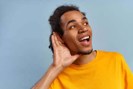 Inquisitive young African American man in yellow t-shirt overhears a secret conversation on blue background. The man put his hand to his ear to hear better about discounts or sale. Free space for text