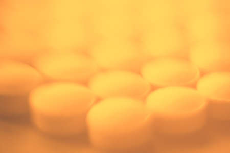 Close up unfocused yellow medical pills background.