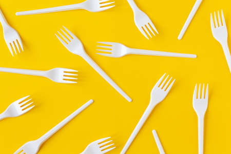 White plastic forks on vibrant yellow background. Flatlay. Fast food, eco and no plastic concept. Open composition.