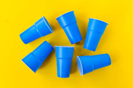 Vibrant blue plastic cups upside down on yellow background. Closed composition image. Top view. No plastic and eco concept.