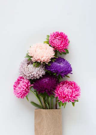 Beautiful colourful asters bouquet packed in craft paper on light gray background.