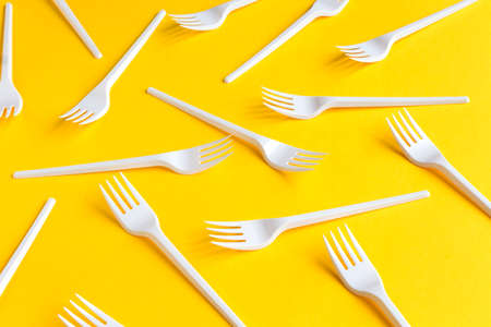 White plastic forks on vibrant yellow background. Fast food, eco and no plastic concept. Open composition.