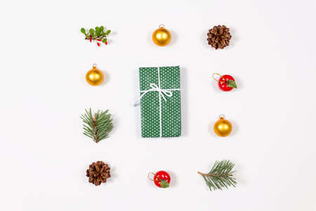 Creative flat lay of winter toys, berries, balls, cones and wrapped with bow gift on white background. Flat lay, top view. Holidays collection.