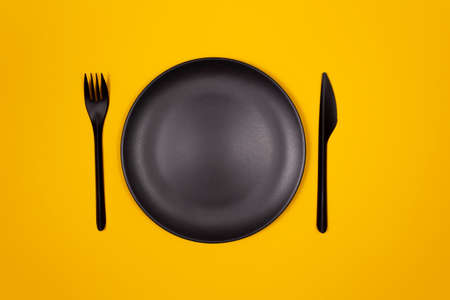 Black plastic plate, fork, knife on yellow background. Creative look at table setting. Fast food and street food concept.