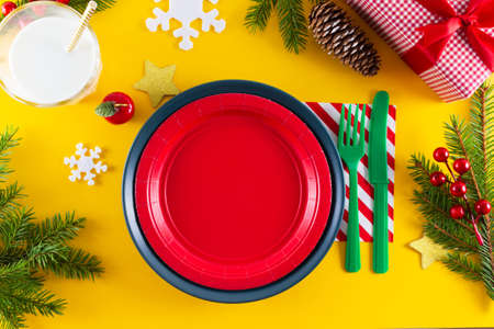 Christmas option of holiday table serving. Christmas kids table setting. Red empty plate, christmas tree branch on yellow background. Holiday concept.