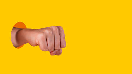 Young woman hand clenched into a fist. Hand sticks out of hole with sharp edges on vibrant yellow background. Equal rights for women concept.