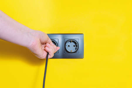 Woman inserts a plug into electric outlet. Black sockets on bright yellow background. Plug and wall socket installation.