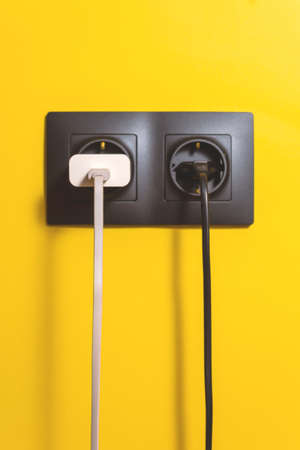 Doubled black socket on yellow wall. Conceptual photo of electricity use in today's life of every person. Different color wires.