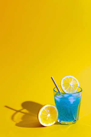 Crazy blue cocktail with lime and chia seeds in glass on orange background. Summer and vacation holidays concept. Vertical format. Copy space.
