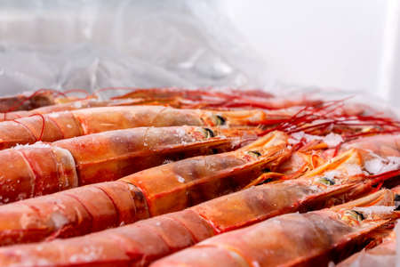 Amazing fresh large frozen shrimps. Pink fresh uncooked shrimps. Close-up. Delivery of frozen seafood to stores in package with hoarfrost on counter. Delicacies, sea food concept.