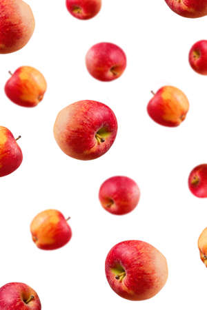 Large ripe red apples falling from top to bottom. Open composition. Close-up. Isolated on white background. Blurred perspective. Stock Photo