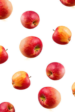 Large ripe red apples falling from top to bottom. Open composition. Close-up. Isolated on white background. Stock Photo