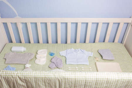 Set of clothing and body care supplies for newborns in baby crib. Collect the bag in the maternity hospital. Accessories for baby care. Preparation before your baby arrives.