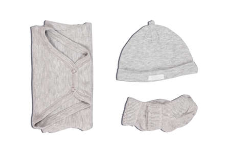 Grey bodysuit, hat and socks for newborn. Isolated on white background with shadow. Unisex outfit for small child.