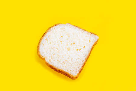 Close up photo of fresh baked toast bread on yellow background. Top view. Bread for breakfast.