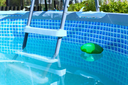 Swimming pool pipe technology. Country pool filtration. Portable small chlorine pool filter. Plastic starcase to country pool. Close-up. Foto de archivo