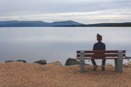 Teenager sitting alone on bench on lake in the evening, looking at horizon and thinking about future. Unity with nature. Loneliness of youth. Psychological assistance to young people. Banque d'images