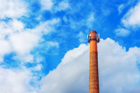Telecommunication tower with antennas on blue sky background. Using old water brick towers on summer blue with clouds sky. Copy space. Small city telecommunications and internet. Banque d'images