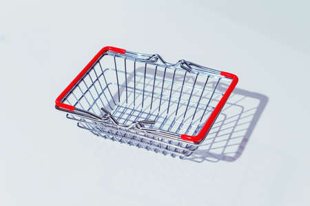 Empty metal shopping basket with red handles on grey background. Living wage. Hard shadows.