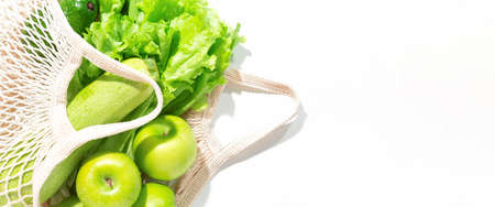 Banner with fresh green fruits and vegetables falling from eco string bag to white background. Top view of salad, zucchini, apples and avocado. Healthy food concept. Left border. Copy space. Foto de archivo