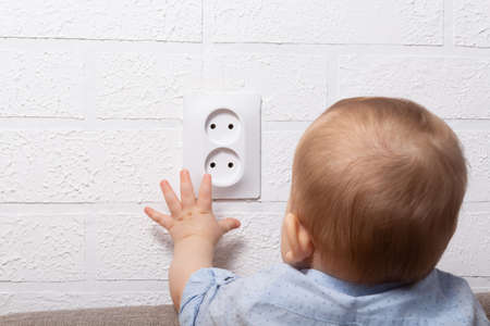 Unrecognizable caucasian boy is playing with open electrical outlet. Baby wires. Dangerous games with open electric socket.
